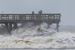 October 7, 2016 - Isle Of Palms, United States - People watch waves bash against the Sea Cabins pier as Hurricane Matthew approaches the coast churning up the Atlantic Ocean October 7, 2016 in Isle of Palms, South Carolina. The hurricane is expected to make landfall near Charleston as a Category 2 storm with strong winds, rain and storm serge. (Credit Image: © Richard Ellis via ZUMA Wire)