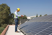 Maintenance worker stands with solar array on rooftop Los Angeles California