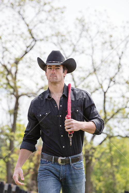 hot cowboy walking on a ranch