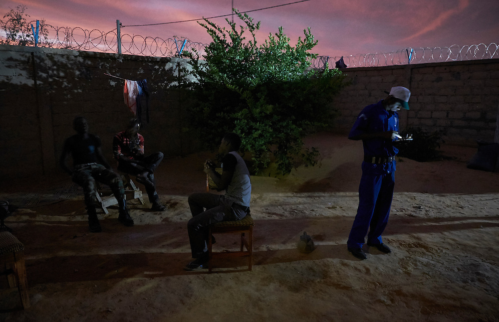 Guards and staff Inside the Caritas headquarters at dusk in Diffa, Niger on February 13, 2016.
