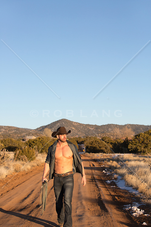rugged muscular cowboy on a ranch with an open shirt