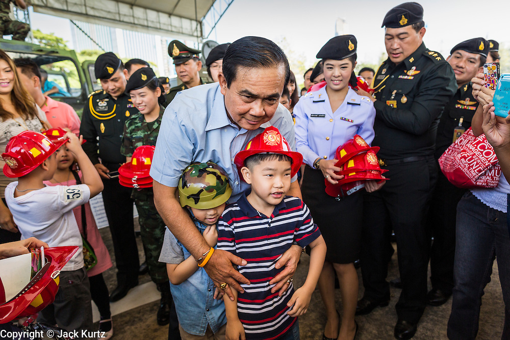 """11 JANUARY 2014 - BANGKOK, THAILAND: General PRAYUTH CHAN-OCHA, Commender in Chief of the Thai Royal Army, give children toy helmets during a Children's Day fair in Bangkok. The Royal Thai Army hosted a """"Children's Day"""" event at the 2nd Cavalry King's Guard Division base in Bangkok. Children had an opportunity to look at military weapons, climb around on tanks, artillery pieces and helicopters and look at battlefield medical facilities. The Children's Day fair comes amidst political strife and concerns of a possible coup in Thailand. Gen Prayuth has issued mixed signal on a coup at one point saying there wouldn't be one, and later saying he wouldn't talk about a possible coup. Earlier in the week, the Thai army announced that movements of armored vehicles through Bangkok were not in preparation of a coup, but were moving equipment into position for Children's Day.      PHOTO BY JACK KURTZ"""