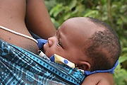 Africa, Tanzania, Lake Eyasi, Portrait of a young Hadza mother breast feeds her baby, A small tribe of hunter gatherers AKA Hadzabe Tribe
