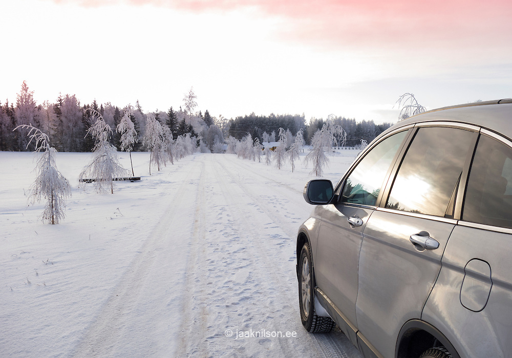 Parked car on snowy rural road in Estonia. White frost, snow covered trees by alley. Evening light reflecting on car glass.