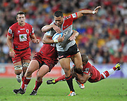 Robbie Fruean is caught in the tackles of Will Genia (low) and Greg Holmes  (high) ~ Super 15 rugby (Round 15) - Reds v Crusaders played at Suncorp Stadium, Brisbane, Australia on Sunday 29th May 2011 ~ Photo : Steven Hight (AURA Images) / Photosport