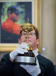 Hamish Wilson from Bonham's with the replica Ryder Cup presented to Sergio Garcia in 2001,  which is expected to fetch up to £8000 GBP in Bonham's sporting goods sale in front of a painting of Tiger Woods which is also in the sale.<br /> <br /> © Dave Johnston/ EEm