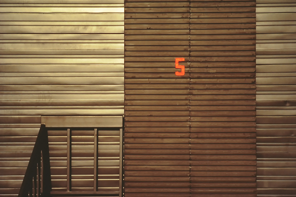 Corrugated metal building with loading bay door number 5 at a Houston, Texas industrial park shipping,loading, delivery dock for freight and cargo area.