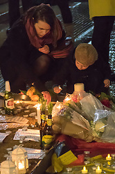 Trafalgar Square, London, March 24th 2016. A other and her little boy light a candle as people gather in London's Trafalgar Square in memory of those who lost their lives in the Brussels terror attacks on March 22nd in which 31 people were killed and dozens injured.