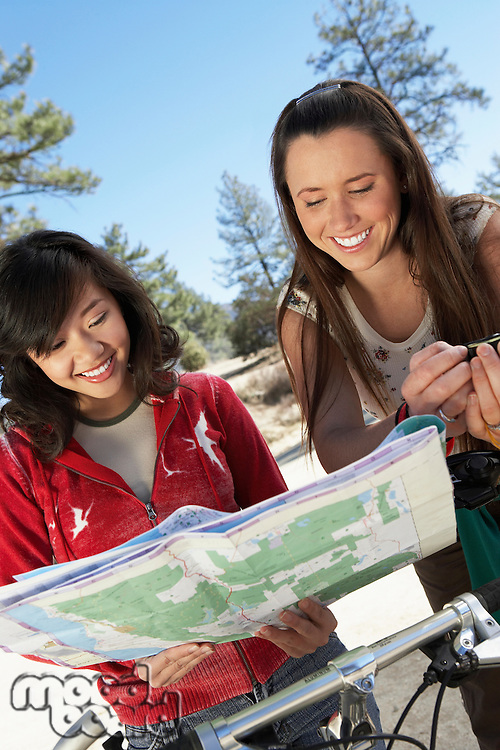 Two young women standing with mountain bikes reading map.