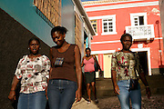 Young women walking on Vila do Maio (Maio's Village) narrow streets. Usually buidings are colourfully painted and people are very friendly to visitors. Maio island has about 7.000 inhabitants and is one of the less-known Cape Verdean islands.