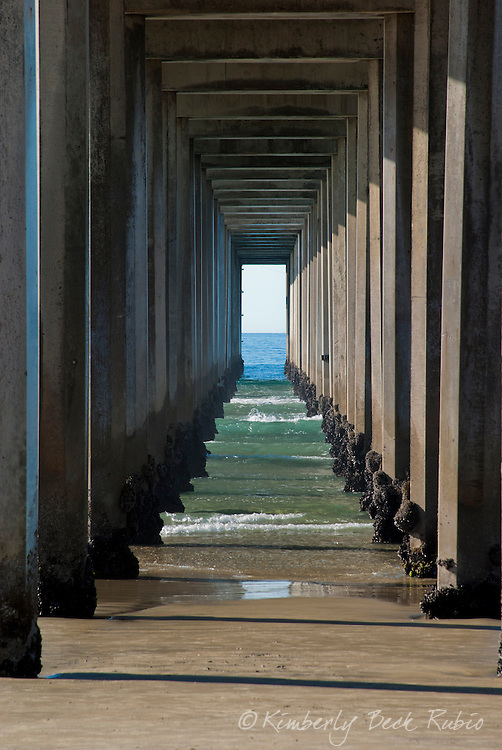 Diminishing perspetive looking through the blue green waters under Scripps Pier in La jolla, California.