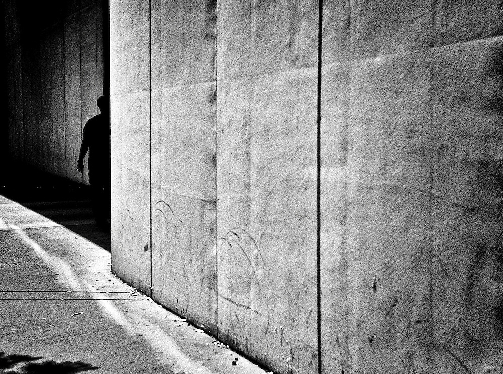 Man standing in the shadows along a sidewalk in an urban area in Charlotte.