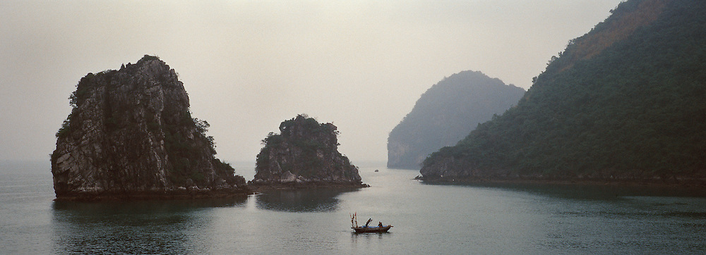 A local fisherman navigates the waters in the early morning mist in Ha Long Bay, Vietnam. The bay consists of a dense cluster of 1,969 limestone monolithic islands. Ha Long Bay, is a UNESCO World Heritage Site, and a popular tourist destination. Ha Long, Bay, Vietnam.  Photo Tim Clayton