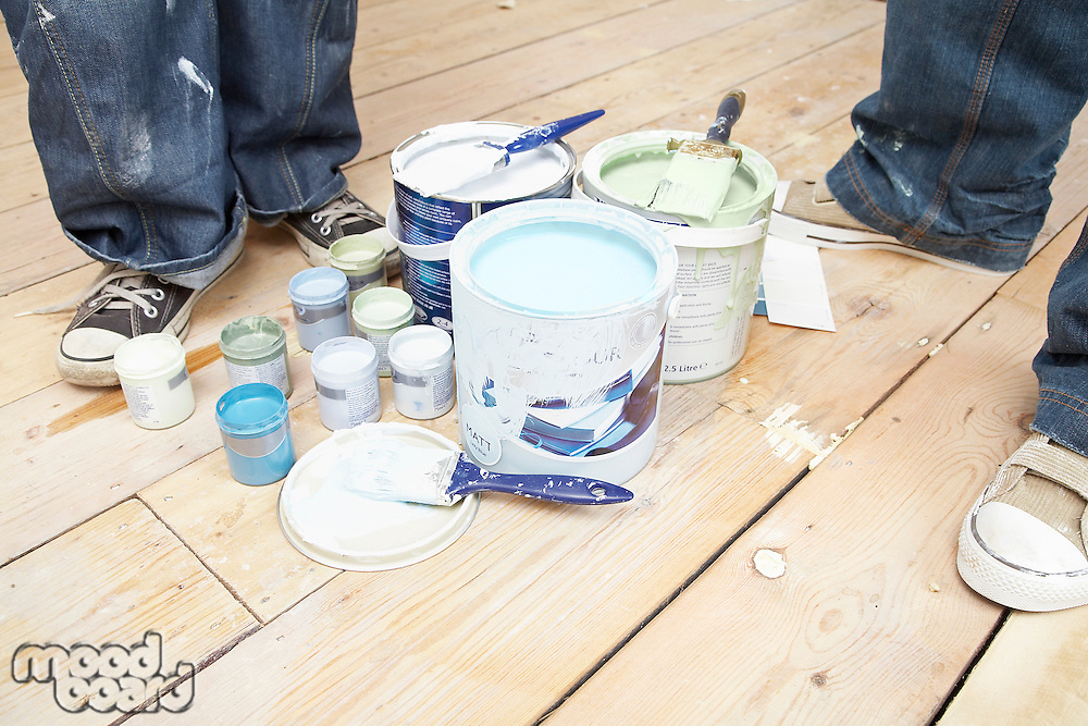 Couple standing next to paint cans on floorboards low section