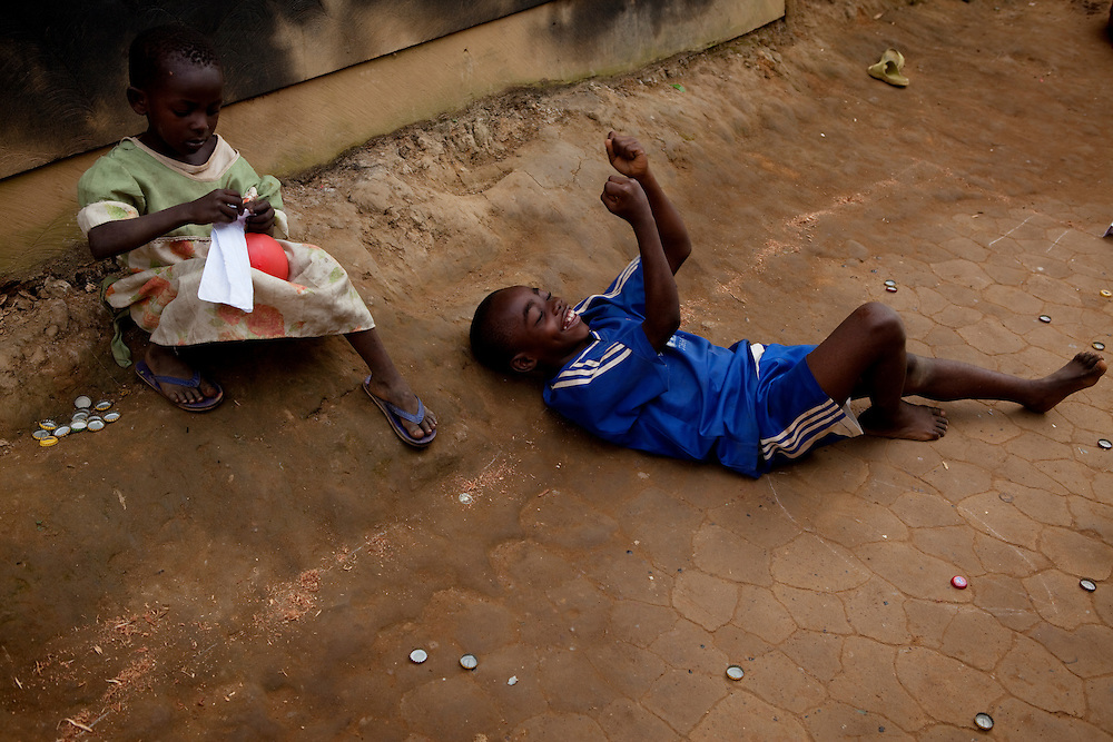 9 year old Dadi celebrates winning a game of bottle cap football over a friend in a poor area of Yaounde. Yaounde, Cameroon.