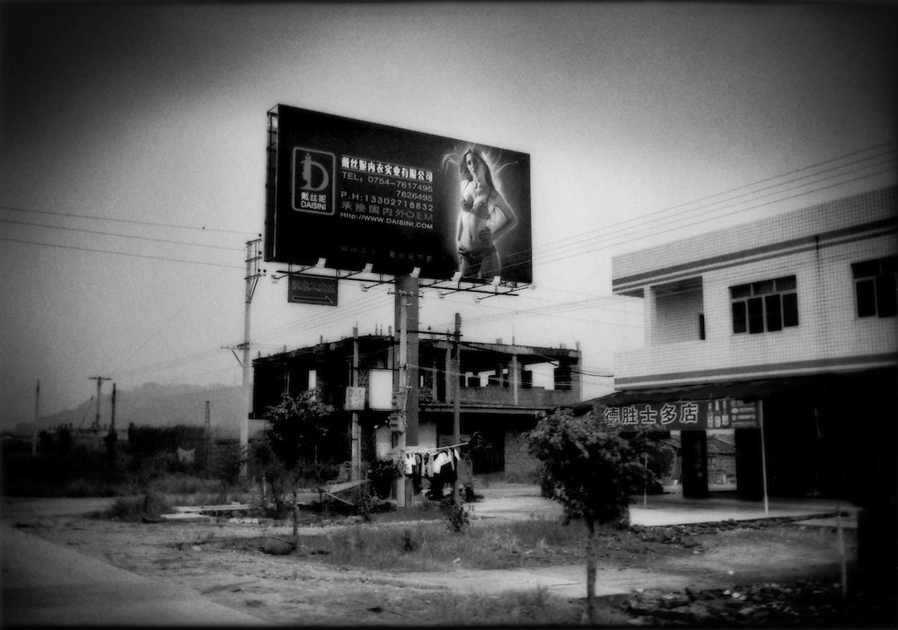 This highway along the coast of Guangdong Province is peppered with dozens of billboards of women dressing is revealing lingerie because the former farming villages are now known for their textile factories producing women's undergarments, south of Shantou, China.