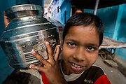A kid is carries a pot, to fetch some milk or water for his family.