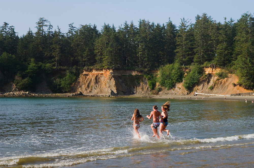 Group of teenage girls running into the water on the beach at Sunset Bay State Park on the Oregon coast.