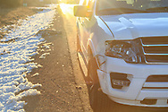 White SUV damaged following collision with deer on a paved road