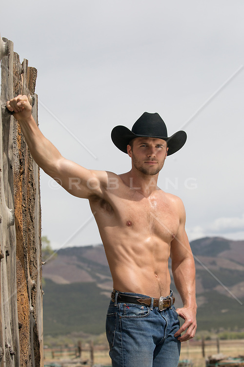 shirtless cowboy outdoors leaning on a fence