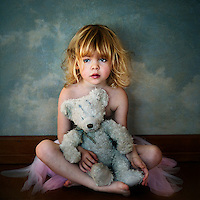 A young girl lost in thoughts holding a teddy and wearing a ballerina tutu