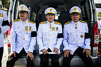 BANGKOK, THAILAND - October 26, 2017: Three uniformed officials wait on the sidelines of the late king's funeral procession in Bangkok, Thailand. Hundreds of thousands of people, dressed in black, have gathered in Bangkok over a year after the death of Thailand's popular King Bhumibol Adulyadej.  The five-day royal cremation ceremony is taking place between October 25-29 in Bangkok's historic Grand Palace and the Sanam Luang area.