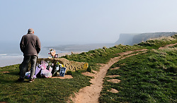 © Licensed to London News Pictures. <br /> 28/03/20167. <br /> Saltburn by the Sea, UK.  <br /> <br /> A man looks at floral tributes left at the top of Huntcliff in Saltburn by the Sea where friends HARRY WATSON and ALEX YEOMAN, both 17, died.<br /> The two teenage boys were found dead at the bottom of the cliffs last Friday.<br /> They are understood to be childhood friends and attended Freebrough College in Middlesbrough.<br /> Teesside Coroners Service have confirmed an inquest into the deaths would be opened for the two friends.<br /> <br /> <br /> Photo credit: Ian Forsyth/LNP
