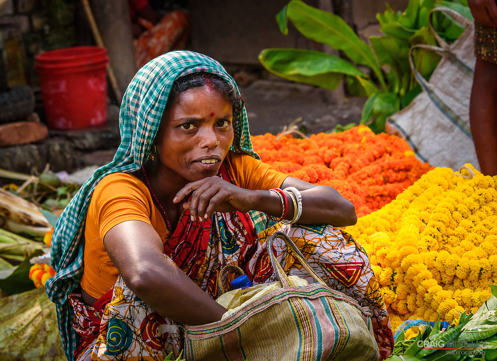 One of the women vendors of the Mullik Ghat, the Kolkata wholesale flower market, with some of the flower garlands that are so popular for their presentation to the gods and temples.<br /> <br /> Nikon D750 100mm  ISO 2500  f8  1/1000s