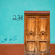 Ornate wooden door and colourful wall of a colonial style buildingin San Christobal, Mexico