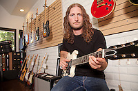 Portrait of serious mid adult man sitting in guitar store