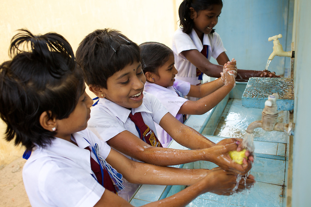 Grade 4 Childrens Brigade students washing their hands in UNICEF-supplied sinks at the K.M. Vivekanana Vidalayam school in Kalmunai, Ampara Dist. <br /> <br /> The Kalmunai community was tsunami affected and for six months the school grounds became an IDP camp. The school continued teaching during this time in a local temple. The school is known as a &quot;Child Friendly School&quot;. Unicef has provided sanitary facilities: boys and girls toilets and hand washing area. Immediately after the tsunami, Unicef supplied books to the school. Unicef has trained teachers in child friendly education and in the establishment of a Children's Brigade. Children's Brigades are a means of promoting hygiene practice in pupils and encouraging them to disseminate messages of hygiene practice and awareness in the wider community.<br /> <br /> Photo: Tom Pietrasik<br /> Ampara District, Sri Lanka<br /> September 29th 2009