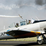 A pilot and his co-pilot taxi to the runway in preparation for a re-enactment of a battle as another pilot flys his plane by in the background at the annual Commemorative Air Force Air Sho.