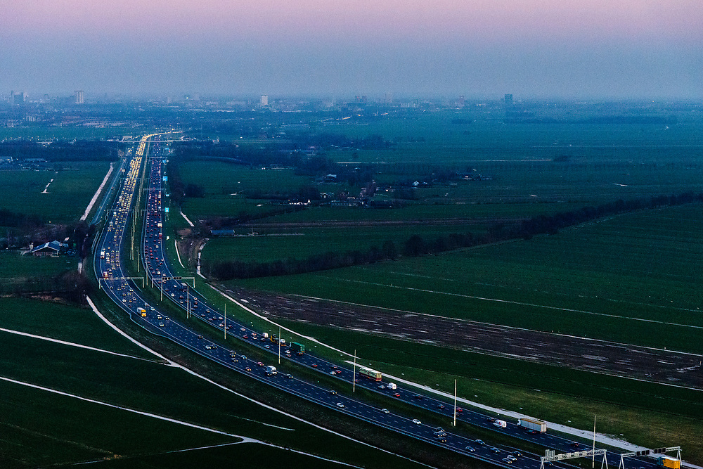Nederland, Zuid-Holland, Woerden , 07-02-2018; verkeer en file op de A12 in de avondschemering en bij zonsondergang. Den Haag aan de verre horizon.<br /> Motorway A12 at sunset, skyline The Hague in the far distance.<br /> luchtfoto (toeslag op standard tarieven);<br /> aerial photo (additional fee required);<br /> copyright foto/photo Siebe Swart