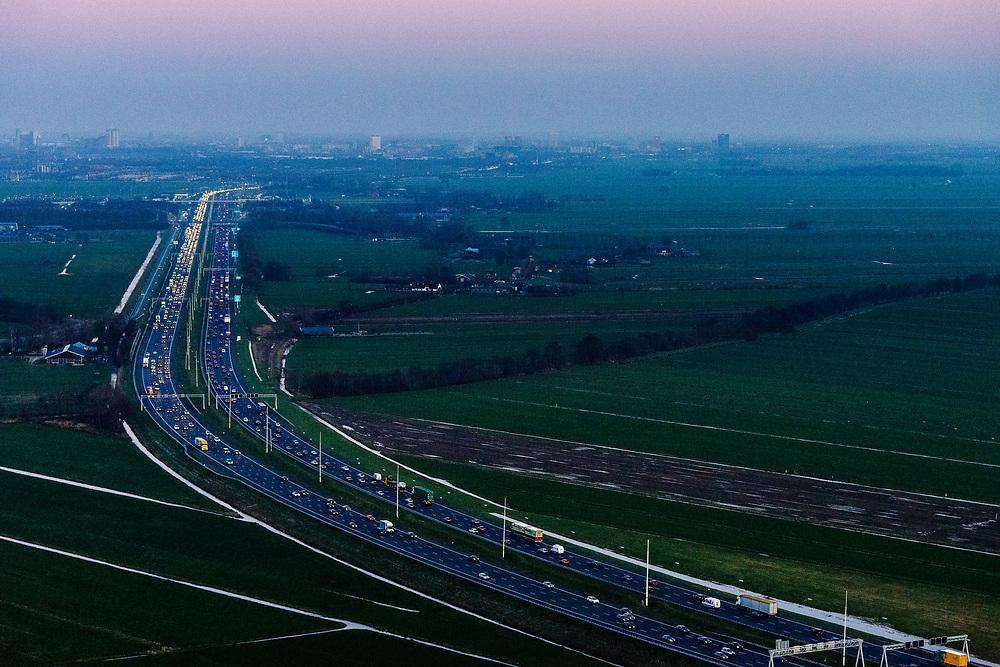 Nederland, Zuid-Holland, Woerden , 07-02-2018; verkeer en file op de A12 in de avondschemering en bij zonsondergang. Den Haag aan de verre horizon.<br /> Motorway A12 at sunset, skyline The Hague in the far distance.<br /> luchtfoto (toeslag op standard tarieven);<br /> aerial photo (additional fee required);<br /> copyright foto/photo Siebe Swart