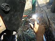 Metal worker welds a metal frame