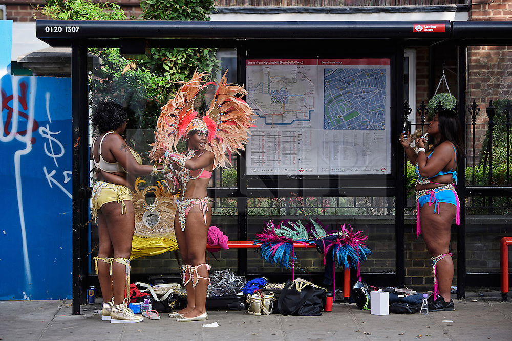 © Licensed to London News Pictures. 29/08/2016. London, UK. Carnival goers prepare their costumes at a bus stop ahead of day two of the Notting Hill carnival, the second largest street festival in the world after the Rio Carnival in Brazil, attracting over 1 million people to the streets of West London.  Photo credit: Ben Cawthra/LNP