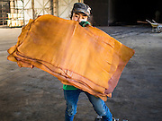 "16 DECEMBER 2014 - CHUM SAENG, RAYONG, THAILAND: A worker hangs rubber sheets to dry before they are put into a smoker at a large rubber plantation near Chum Saeng, Thailand. Thailand is the second leading rubber exporter in the world. In the last two years, the price paid to rubber farmers has plunged from approximately 190 Baht per kilo (about $6.10 US) to 45 Baht per kilo (about $1.20 US). It costs about 65 Baht per kilo to produce rubber ($2.05 US). Prices have plunged 5 percent since September, when rubber was about 52Baht per kilo. Some rubber farmers have taken jobs in the construction trade or in Bangkok to provide for their families during the slump. The Thai government recently announced a ""Rubber Fund"" to assist small farm owners but said prices won't rebound until production is cut and world demand for rubber picks up.    PHOTO BY JACK KURTZ4 - CHUM SAENG, RAYONG, THAILAND: A worker sorts smoked rubber sheets during the quality control process on a large rubber plantation near Chum Saeng, Thailand. Thailand is the second leading rubber exporter in the world. In the last two years, the price paid to rubber farmers has plunged from approximately 190 Baht per kilo (about $6.10 US) to 45 Baht per kilo (about $1.20 US). It costs about 65 Baht per kilo to produce rubber ($2.05 US). Prices have plunged 5 percent since September, when rubber was about 52Baht per kilo. Some rubber farmers have taken jobs in the construction trade or in Bangkok to provide for their families during the slump. The Thai government recently announced a ""Rubber Fund"" to assist small farm owners but said prices won't rebound until production is cut and world demand for rubber picks up.    PHOTO BY JACK KURTZ"