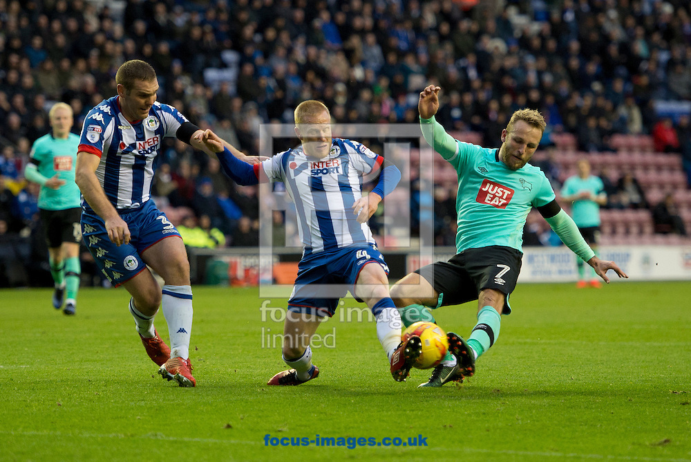 Johnny Russell of Derby County (right) has a shot blacked by David Perkins of Wigan Athletic during the Sky Bet Championship match at the DW Stadium, Wigan<br /> Picture by Russell Hart/Focus Images Ltd 07791 688 420<br /> 03/12/2016