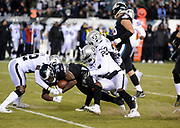 Dec 25, 2017; Philadelphia, PA, USA; Oakland Raiders densive backs Karl Joseph (42), TJ Carrie (38) and safety Reggie Nelson (27) make a stop of Eagles running back Corey Clement (30) during a NFL football game at Lincoln Financial Field. The Eagles defeated the Raiders 19-10. Photo by Reuben Canales