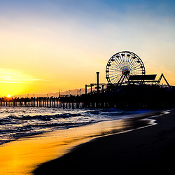 Santa Monica Pier sunset panoramic photo. Panorama picture ratio is 1:3. Santa Monica Pier is a landmark that has an amusement park with a ferris wheel, roller coaster, restaurants, and other attractions.