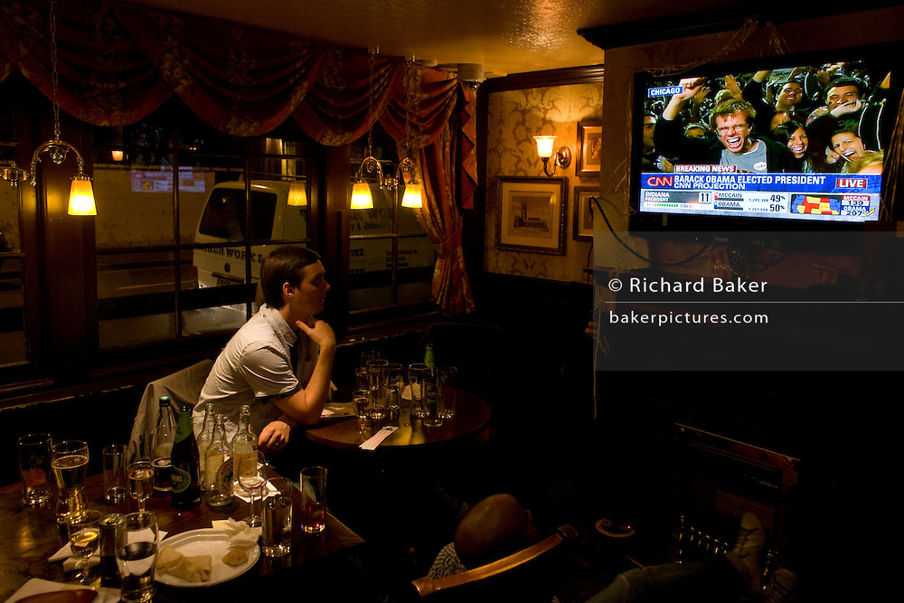 Young man watches TV after Barack Obama is declared Presidential election winner by CNN during overnight party in London