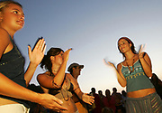 Three cute hippy girls dancing and clapping, Sunset beach party, Benirras Beach, Ibiza, July 2006