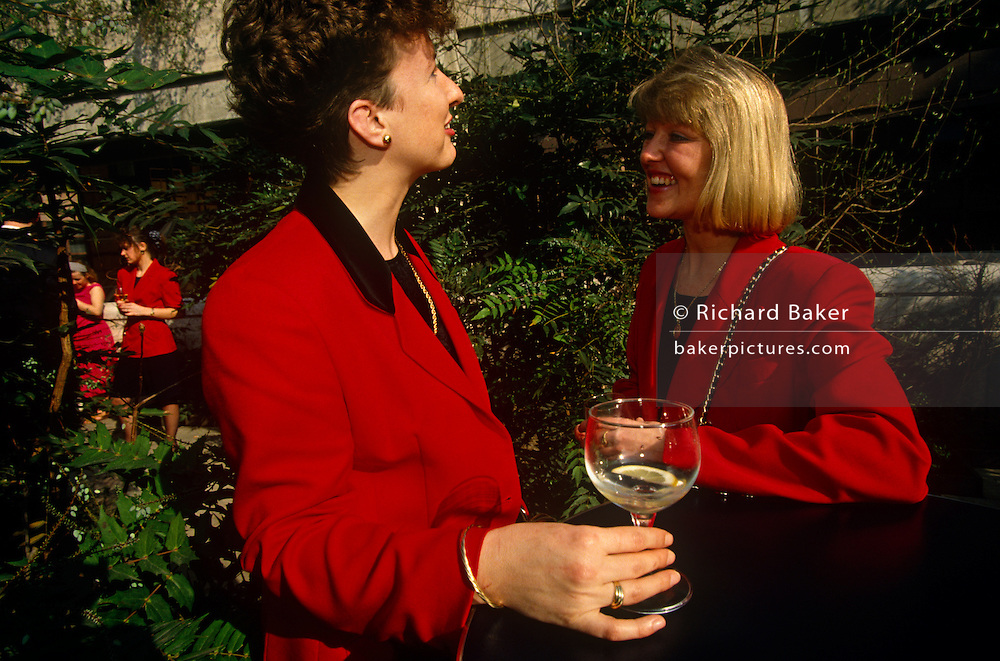 Two ladies stand outside of a bar to sip lunchtime drinks in Broadgate, City of London. Dressed in matching scarlet red jackets, the brunette and the blonde look relaxed in the warm mid-day sunshine during a warm spell in the capital. The nearest woman holds the remains of a gin and tonic whose lemon slice  is at the bottom of her glass while her friend or colleague, with wide shoulder pads and gold chain strap for her bag draped over across a shoulder, smiles to show white teeth. In the background are other women who wear the same red clothes and these primary colours are set amongst the deep green foliage of the bar's plants. .