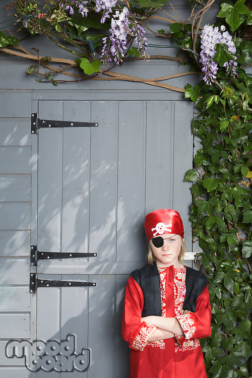 Portrait of young boy (7-9) in pirate costume by shed