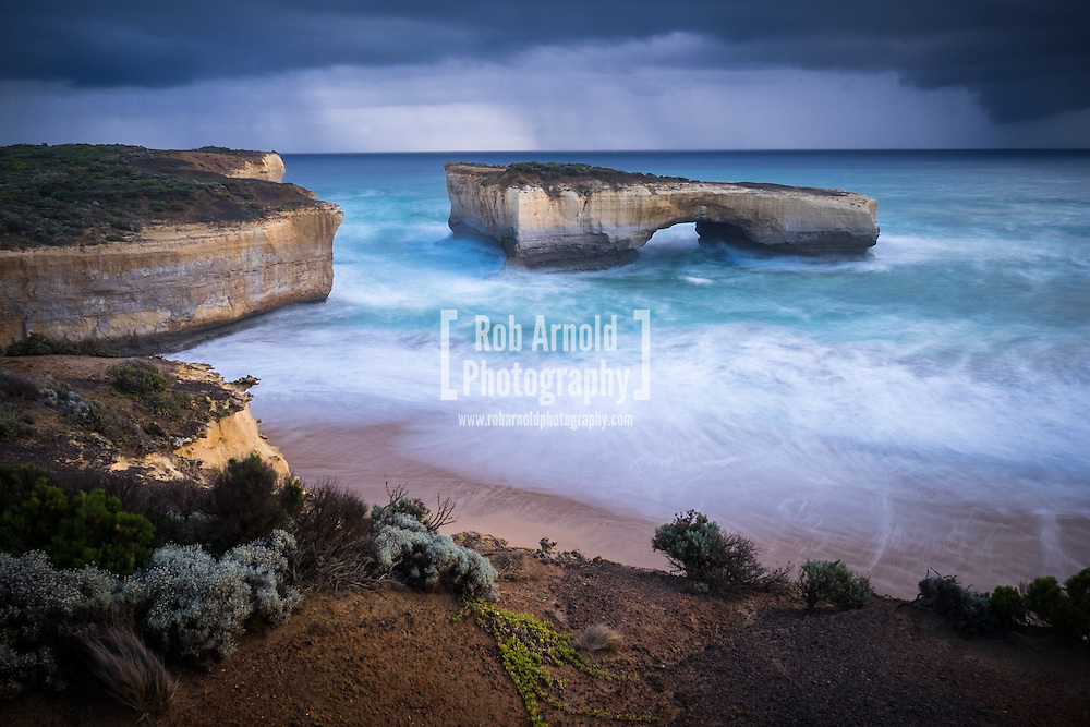 Rain showers pass the scenic natural arch formation, London Bridge (Arch), near Port Campbell along Victoria's Great Ocean Road. The arch was once connected to the mainland by a rock bridge, which unexpectedly collapsed on 15th January 1990, leaving two people stranded on the outer stack, who were later rescued by helicopter.