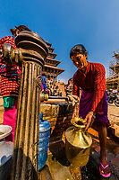 Nepali women fill jugs for their home's daily water needs at a communal well in Taumadhi Square, Bhaktapur, Kathmandu Valley, Nepal.