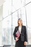 Confident businesswoman looking away while holding folder at office lobby