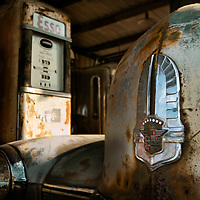 A rusting classic American luxury car rusting away in an old gas station.