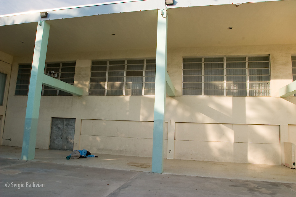 A homeless man sleeps in the courtyard of a school in SoBe, Miami, Florida.