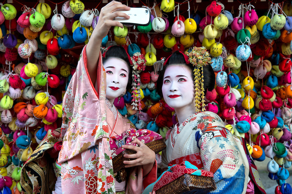 "Two japanese girls take a Selfie in front of the Yasaka Koushindou temple in Kyoto.  The colored pockets are called ""Kukurizaru"".  It is said that if you dangle a written wish, it will come true."